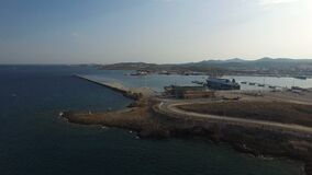 Flying over water towards port docks, containers, cargo ships. Flight over waters of Aegean sea towards docks with containers, loaders, industrial machinery stock footage