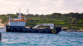 Flying over the water with views of the submarine and green relief land. Sea, river, tug, walk on water, cargo, sunny. Flying over the water with views of the stock footage
