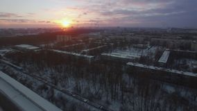 Flying over winter city and moving cargo train. St. Petersburg scene at sunrise. Aerial view of St. Petersburg in winter morning. Snowy roofs, moving cargo train stock footage