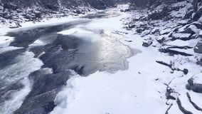 Flying over a winter river in the mountains. stock footage
