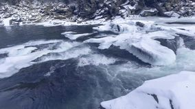 Flying over a winter river in the mountains. stock video footage