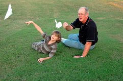 Flying paper airplanes. A boy and his grandfather flying paper airplanes together in the grass Stock Photos