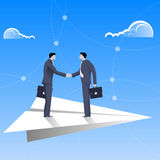 Flying on paper plane business concept. Confident businessmen in business suit shaking each other hands flying on paper plane. Deal, agreement, unity, pact Royalty Free Stock Photography
