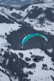 Flying paraglider. Paraglider flying above the winter mountains Stock Photo