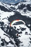 Flying paraglider. Paraglider flying above the winter mountains Stock Image