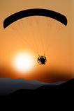 Flying paraglider silhouette at sunset Stock Photo