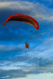 Flying. A paramotor flying high in the sky stock image