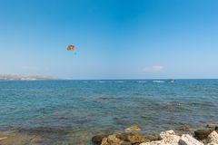 Flying paratrooper with full color parachute, isolated on a blue sky near Rhodes island, Greece Stock Photography