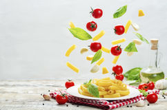 Flying pasta with tomatoes; garlic; cheese and basil Royalty Free Stock Photography