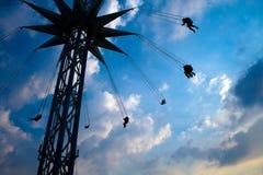 Flying people on swinging carousel stock photography