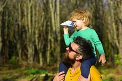 Flying is the perfect vocation for a man who wants to feel like a boy. Little son dream of flying on fathers shoulder. Flying is the perfect vocation for a men royalty free stock image