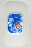 Flying pig. Illustration of pig flying in blue sky and cloudscape viewed from aircraft window Royalty Free Stock Photography