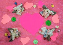 Flying pigs around a pink heart wth flowers - room for text royalty free stock photo