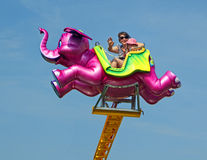 Flying pink elephant fairground ride. Photo of a little girl and mother at whitstable  kent fairground park on a flying pink elephant ride on 17th may 2014.photo Stock Image