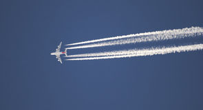 Flying plane. If the airplane leaves a long trail Stock Photography