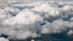 Clouds seen from flying plane. Skyscape with cloud from the plane window midair. Spectacular view from the window of an