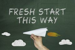 Flying plane and Fresh start this way concept on green blackboard Stock Images