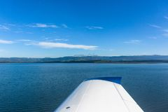 Flying Plane Low Dam Waters Shoreline Royalty Free Stock Photography