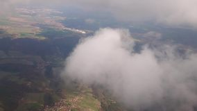 Flying in a plane in the middle of the clouds, the landscape is visible. stock video footage