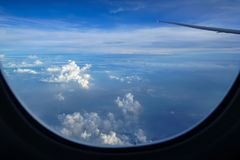 Flying on the plane seeing sunrise light on abstract white cloud and shades of blue sky background with airplane wing. Flying on the plane seeing beautiful stock photo