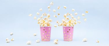 Flying Popcorn in a bright glass and on a blue background. Copy space stock photo