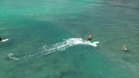 Flying POV, Stand up paddle SUP surfer riding wave off the coast of Honolulu, Hawaii, in aquamarine water, slow motion _