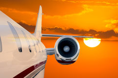 Flying Private Jet Airplane with Sunset background. Closeup of the side of a private jet airplane flying soaring through the air with a beautiful orange sunset Stock Photo