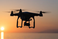 Flying the quadcopter at sunset. Silhouette of a quadrocopter on sunset over the sea Royalty Free Stock Photography