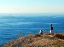 Flying radio controlled plane. Young child with friend flying radio controlled plane off cliffs over sea Stock Photo
