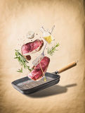 Flying raw beef meat steaks, with herbs, oil and spices with grill pan and kitchen utensils, at natural beige background, front vi Stock Images