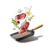 Flying raw beef steaks, with herbs, oil and spices with grill pan and kitchen utensils, isolated on white background, front view. Flying food concept Royalty Free Stock Photos