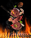 Flying raw milled beef meat with ingredients above grill fire. Flying raw milled beef meat, with ingredients for cooking above grill fire. Freeze motion of Royalty Free Stock Images