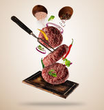 Flying raw milled hamburger meats with ingredients Royalty Free Stock Photo