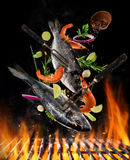 Flying raw whole bream fish and prawns with ingredients above grill fire. Flying raw whole bream fish and prawns, with ingredients for cooking above grill fire Royalty Free Stock Photo