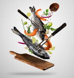 Flying raw whole bream fish and prawns with ingredients Royalty Free Stock Images