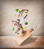 Flying Raw Whole Trout Fishes With Vegetables, Oil And Spices Ingredients Above Wooden Cutting Board For Tasty Cooking On Desk Kit