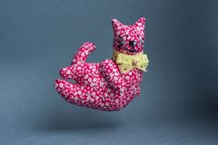 Flying red cat. A handmade toy with a bow around his neck. From a cloth with a pattern, soft. Kind, pleasant, smiling cat Royalty Free Stock Photo
