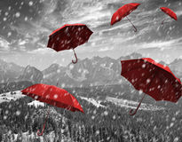 Flying red umbrellas in the mountains during a storm Stock Photo