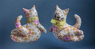 Flying reddish-brown cats. Two handmade toys with a bow around his neck. From a cloth with a pattern, soft. Kind, pleasant, smiling cats Royalty Free Stock Images