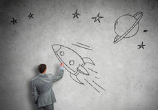 Flying rocket. Rear view of businessman drawing rocket on wall Stock Images