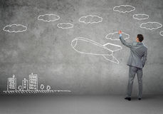 Flying rocket. Rear view of businessman drawing rocket on wall Stock Photos