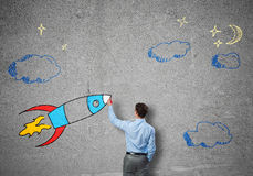 Flying rocket. Rear view of businessman drawing rocket on wall Royalty Free Stock Images