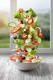 Flying Salad On Wood Against Window Stock Image
