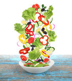 Flying  salad with plate on wooden table Royalty Free Stock Photography