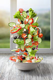Flying salad on wood against window Stock Image
