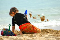 Flying sand. 6 year old boy throwing sand out of shovel at the beach Stock Photos