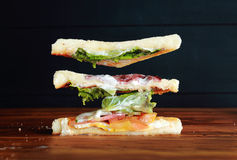 Sandwich components. Slices of bread and sandwich components floating in air over wooden table on black background royalty free stock photo