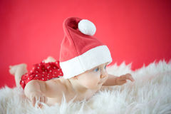 Flying Santa. Baby girl on red background Stock Photography