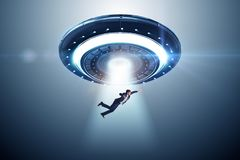 The flying saucer abducting young businessman stock image