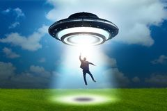 Flying saucer abducting young businessman stock image